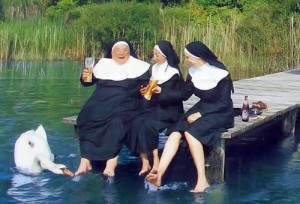 Three nun in traditional habit sit on the end of a pier.  On nun is surprised by a swan that is biting her foot.
