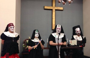 Four nuns in white makeup and black habits stand in front of an alter.