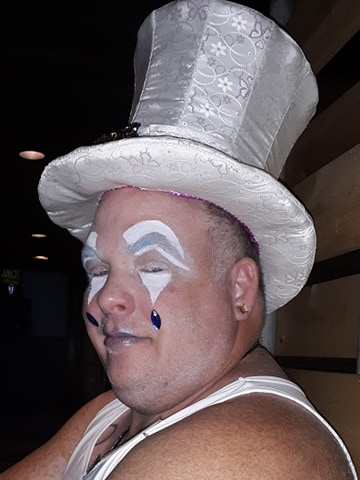 A close up of a person's head with white makeup and blue jewels attached to the face. They are wearing a white top hat